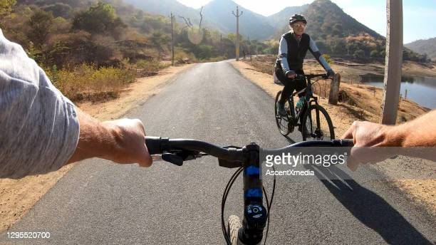 pov of riding bicycles along rural desert road, towards each other - desert stock pictures, royalty-free photos & images