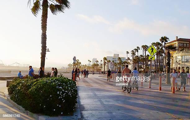 Riding bikes and walking at Santa Monica Beach at sunset