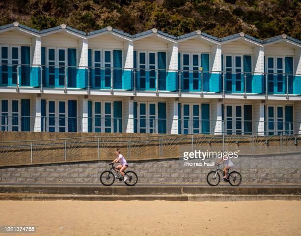 ドーセットのプールのビーチ小屋の前で自転車に乗る - プール湾 ストックフォトと画像