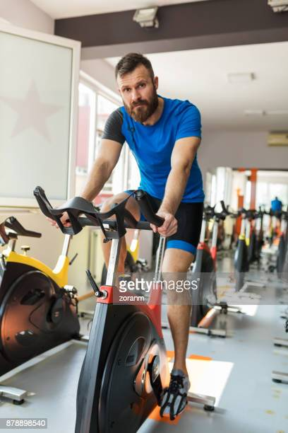 Riding exercise bike in gym