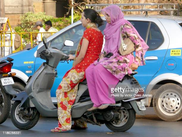 riding in mumbai. two women on a scooter in the fort district in mumbai, maharashtra, india - victor ovies fotografías e imágenes de stock