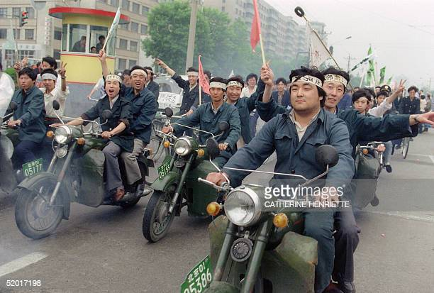 Riding motorbikes Chinese workers parade through Beijing streets 18 May 1989 in support of student hunger strikers gathered at Tiananmen Square the...