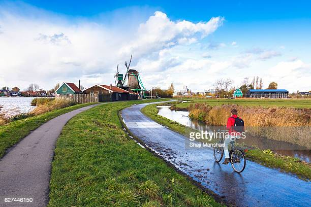 riding through the beautiful villages of amsterdam , zaanse schans windmill villages - dutch windmill stock photos and pictures