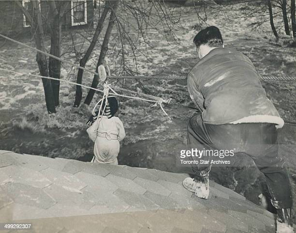 Riding to safety in an improvised breeches buoy Robin Thompson three was the first to be rescued by this method in the Long Branch flood [Incomplete]
