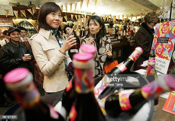 Rie Takahashi and Naoko Takarada of Japan taste glasses of Beaujolais Nouveau 2005 at SherryLehmann wine and spirits November 17 2005 in New York...