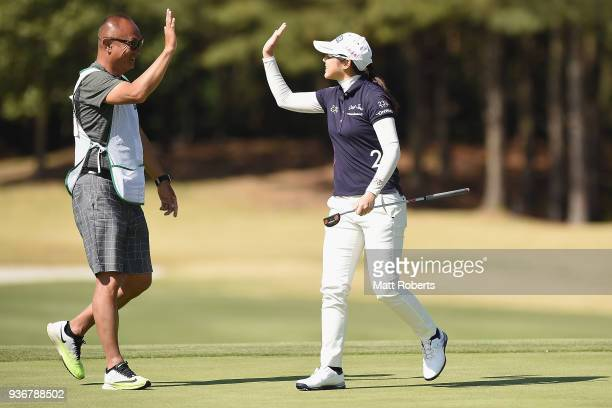 Rie Tsuji of Japan celebrates with her caddie on the 9th green during the first round of the AXA Ladies Golf Tournament In Miyazaki at the UMK...