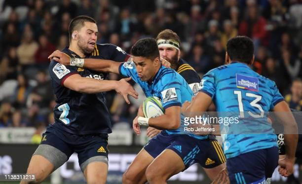 Rieko Ioane of the Blues is wrapped up by Tyrel Lomax of the Highlanders during the round 10 Super Rugby match between the Highlanders and the Blues...