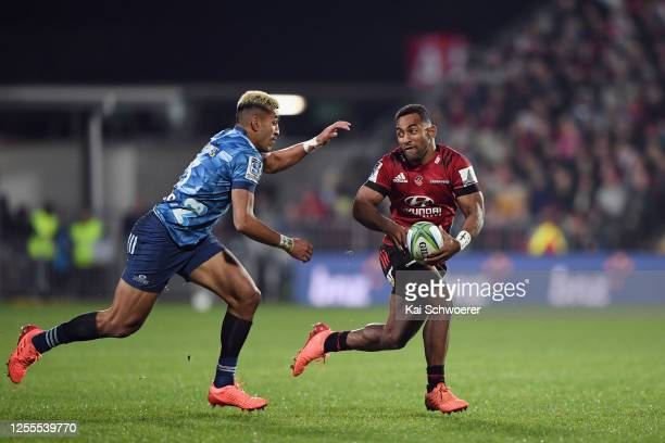 Rieko Ioane of the Blues looks on as Sevu Reece of the Crusaders charges forward during the round 5 Super Rugby Aotearoa match between the Crusaders...
