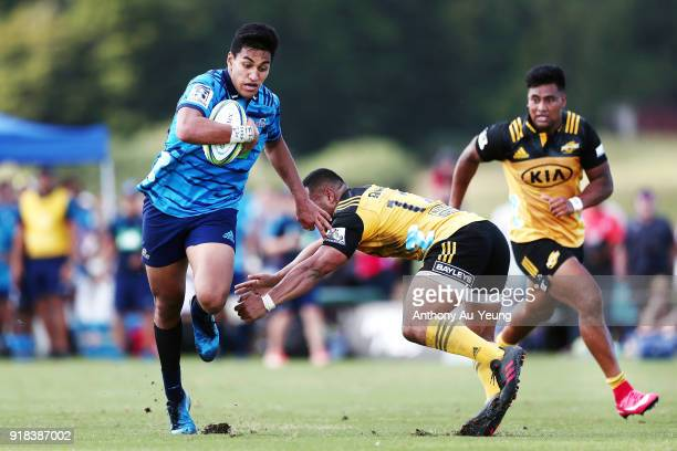 Rieko Ioane of the Blues makes a break against Ngani Laumape of the Hurricanes on his way to score a try during the Super Rugby trial match between...