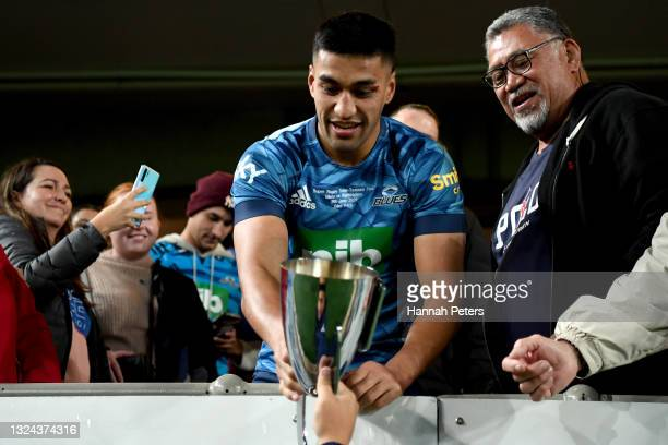 Rieko Ioane of the Blues takes the trophy into the crowd to celebrate after winning the Super Rugby Trans-Tasman Final match between the Blues and...