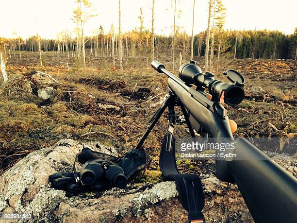Rifle And Binoculars On Rock In Forest