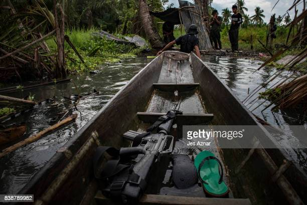 Rifle belonging to Moro Islamic Liberation Front figher sits on a boat Moro Islamic Liberation Front Fighters and local police walk through at the...