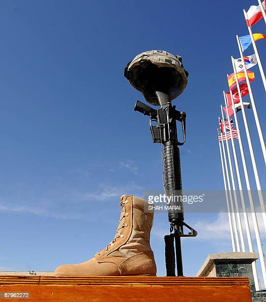 Rifle, helmet and pair of boots lie as a token of respect during a ceremony at Bagram air base, about 50 kms north of Kabul on May 25, 2009. US...
