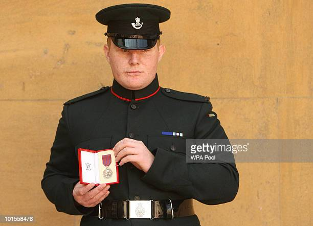 Rifleman Paul Jacobs holds the George Medal awarded to him for his bravery in Afghanistan which was conferred to him by Britain's Queen Elizabeth II...