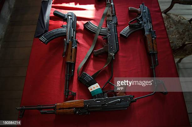 AK47 rifles one bearing the preBaath Syrian flag that was adopted by the Syrian revolution during the uprising are pictured on a table during the...