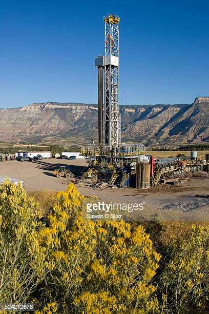 A rig drills for natural gas framed by the cliffs of the Roan Plateau and a hill blooming with Rabbit Brush New wells will add to some 7500 operating...
