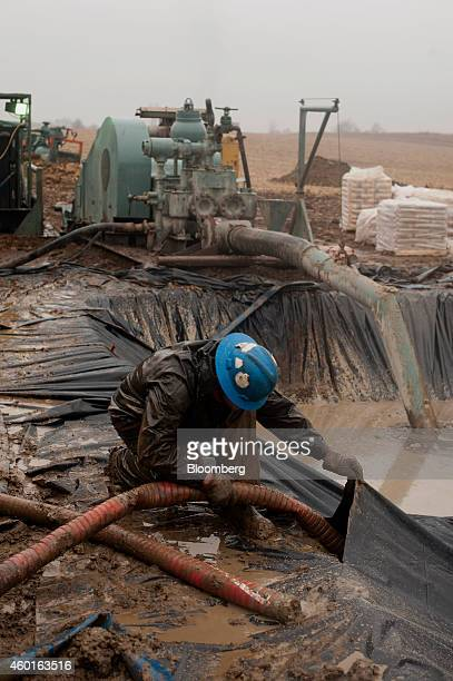 A rig hand slips a three inch pump into the pit to move in water to reduce the fruition on the drill head at a Knox Energy Inc oil drilling site in...
