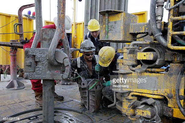 Rig hands from Cofor and Schlumberger Ltd work on the floor section of the drilling rig at the geothermal energy extraction site operated by Semhach...