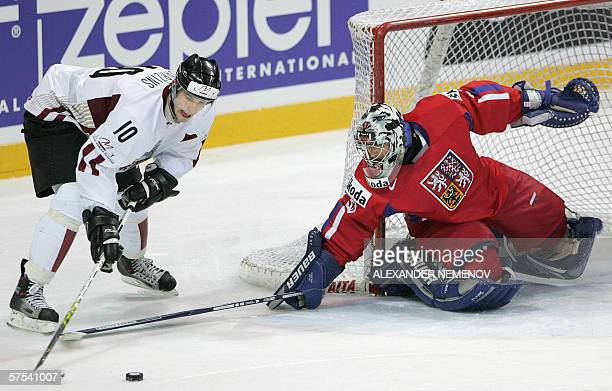 Czech goalie Milan Hlinicka fights for the the puck with Latvian Lauris Darzinis during their preliminary round match of the Internetional Ice Hockey...