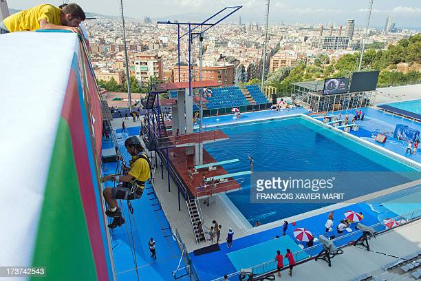 A rigger fixes flags at the Montjuic swimming pool on July 17 two days before the start of the 15th FINA World Championships in Barcelona AFP PHOTO /...