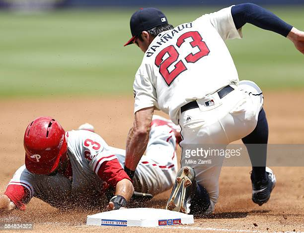 Right fielder Aaron Altherr of the Philadelphia Phillies is tagged out by third baseman Chase d'Arnaud of the Atlanta Braves as he tries to advance...