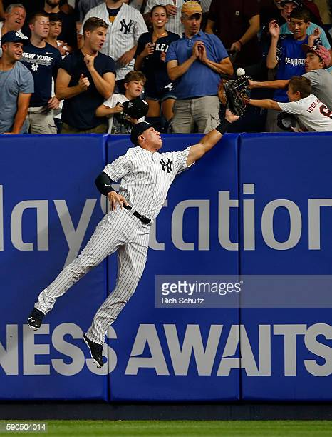 Right fielder Aaron Judge of the New York Yankees attempts to make a catch on a ball for a three run home run by Troy Tulowitzki of the Toronto Blue...