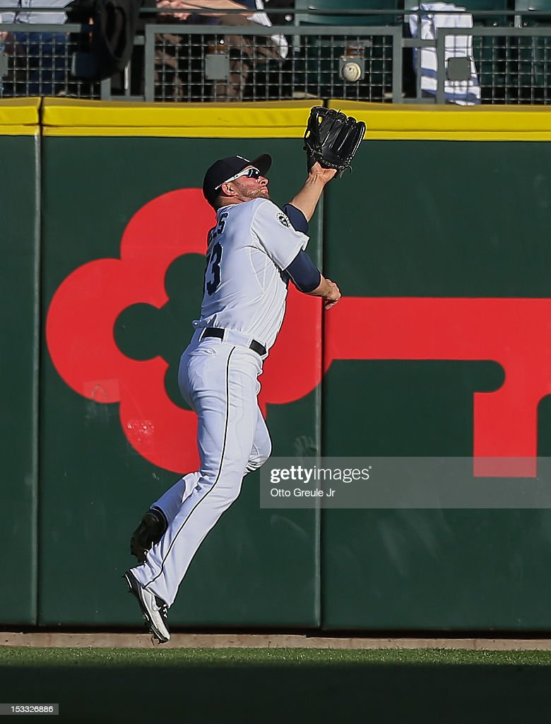 Right fielder Casper Wells #33 of the Seattle Mariners makes a leaping catch on a ball hit by Alberto Callaspo of the Los Angeles Angels of Anaheim at Safeco Field on October 3, 2012 in Seattle, Washington.
