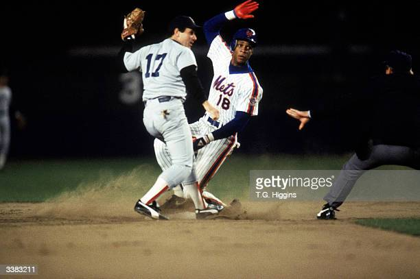 Right fielder Darryl Strawberry of the New York Mets slides into second base safely under the tag of Marty Barrett of the Boston Red Sox during game...