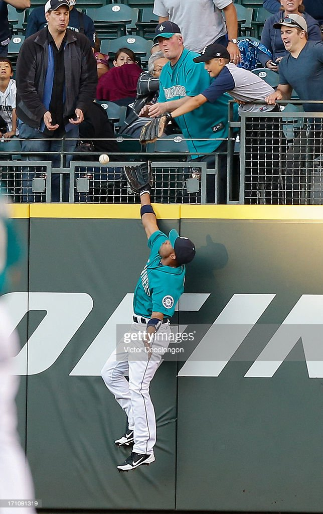 Right fielder Endy Chavez #9 of the Seattle Mariners leaps for a home run ball by Coco Crisp of the Oakland Athletics at Safeco Field on June 21, 2013 in Seattle, Washington. The Athletics defeated the Mariners 6-3.