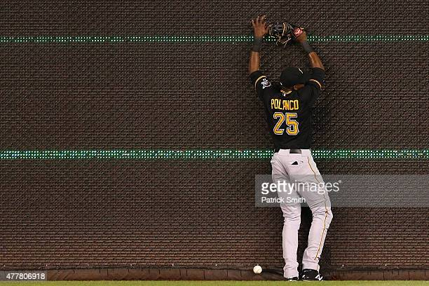 Right fielder Gregory Polanco of the Pittsburgh Pirates crashes into the outfield wall after he missed an RBI triple hit by Danny Espinosa of the...