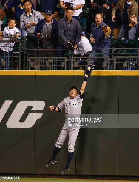Right fielder Ichiro Suzuki of the New York Yankees makes a leaping catch at the wall on a ball off the bat of Stefen Romero of the Seattle Mariners...