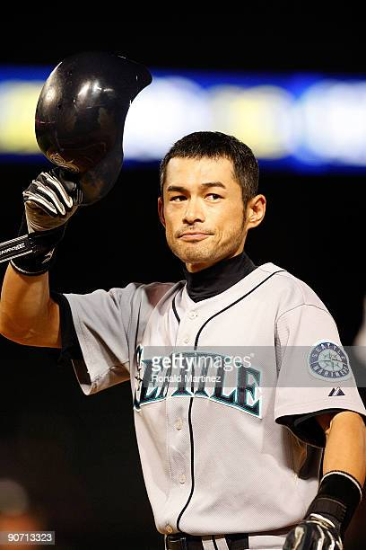 Right fielder Ichiro Suzuki of the Seattle Mariners tips his helmet after hitting his 200th hit of the season against the Texas Rangers on September...