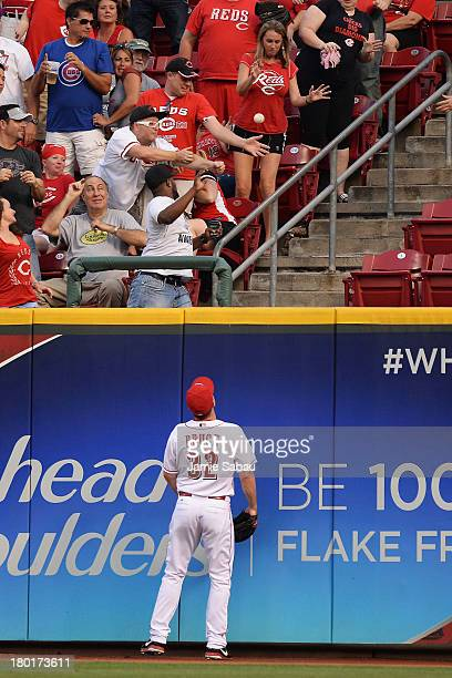 Right fielder Jay Bruce of the Cincinnati Reds watches a home run hit by Ryan Sweeney of the Chicago Cubs in the second inning sail over the wall at...