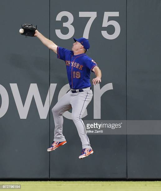 Right fielder Jay Bruce of the New York Mets jumps and stretches but does not catch a double hit by right fielder Nick Markakis of the Atlanta Braves...