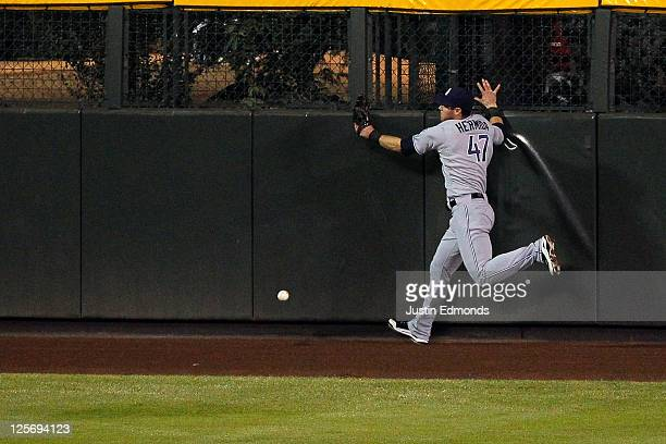 Right fielder Jeremy Hermida of the San Diego Padres hits the wall while trying to make a play on a triple by Eric Young during the sixth inning...