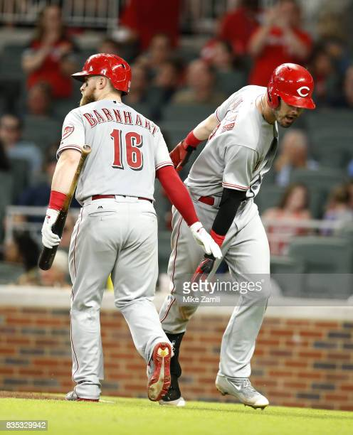 Right fielder Jesse Winker of the Cincinnati Reds is congratulated by teammate and catcher Tucker Barnhart after Winker's solo home run in the sixth...