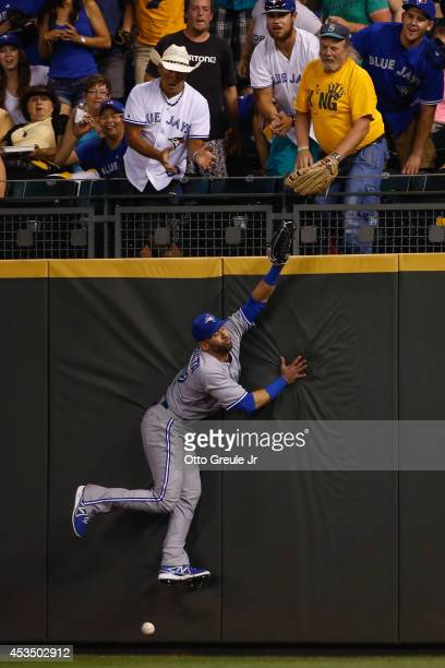 Right fielder Jose Bautista of the Toronto Blue Jays misses a ball off the bat of Mike Zunino of the Seattle Mariners that went for an RBI triple in...