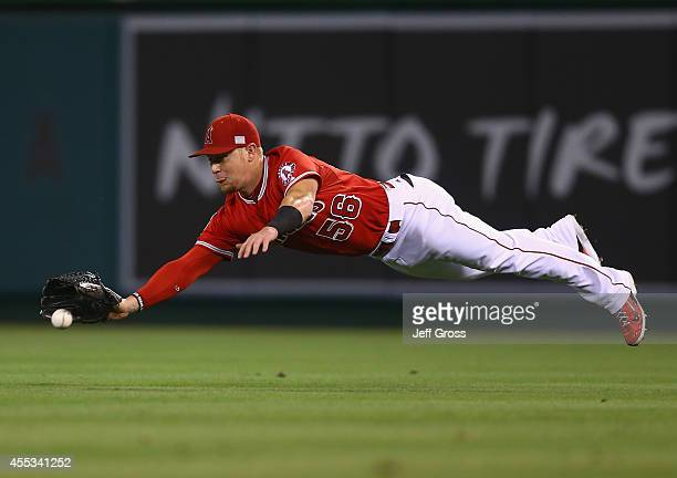 Right fielder Kole Calhoun of the Los Angeles Angels of Anaheim dives for a ball hit by Jose Altuve of the Houston Astros but isn't able to make the...