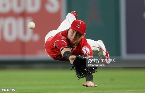 Right fielder Kole Calhoun of the Los Angeles Angels of Anaheim dives but can't catch a ball that went for a single off the bat of Jonathan Lucroy of...