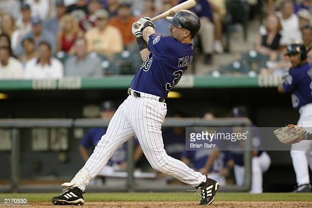 Right fielder Larry Walker of the Colorado Rockies hits a two-run double against the San Francisco Giants during the MLB game at Coors Field on July...