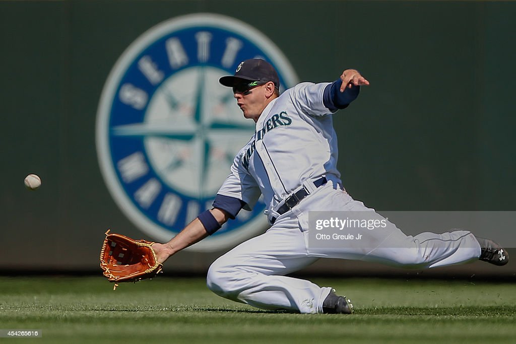 Right fielder Logan Morrison #20 of the Seattle Mariners makes a sliding catch on a ball off the bat of Jim Adduci of the Texas Rangers in the seventh inning at Safeco Field on August 27, 2014 in Seattle, Washington. The Rangers defeated the Mariners 12-4.