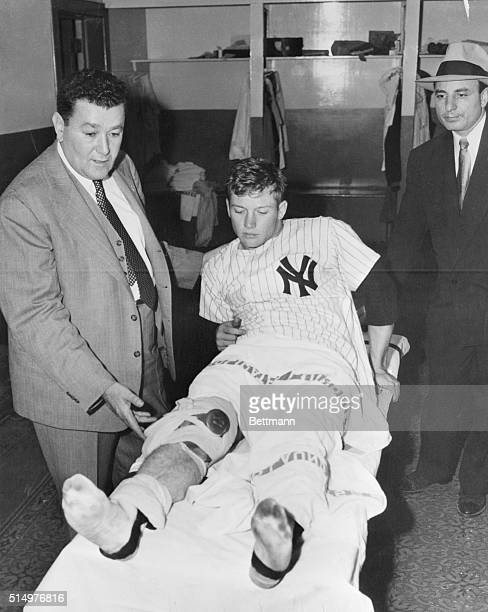 Right Fielder Mickey Mantle of the New York Yankees has his right knee examined here by Dr Sidney Gaynor in the team's dressing room at the Yankee...