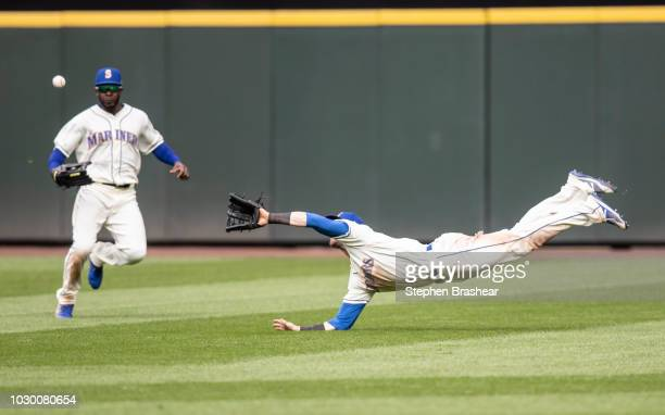 Right fielder Mitch Haniger of the Seattle Mariners makes a diving catch on a ball hit by Giancarlo Stanton of the New York Yankees as center fielder...