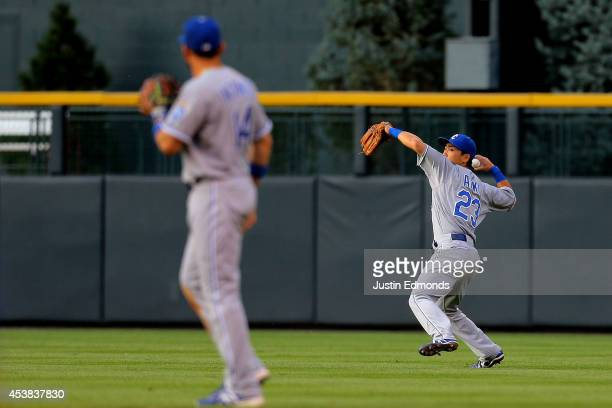 Right fielder Norichika Aoki of the Kansas City Royals throws to third base during the second inning as second baseman Omar Infante looks on against...