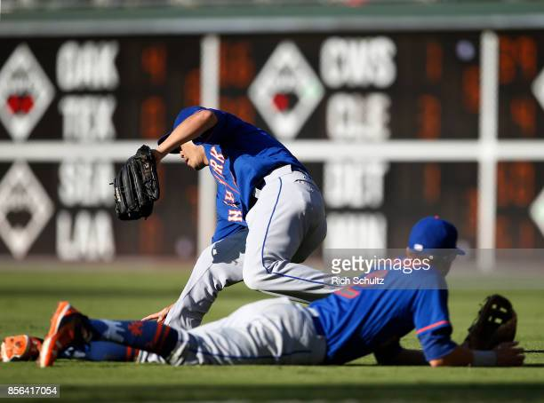 Right fielder Norichika Aoki of the New York Mets pics up the ball that second baseman Gavin Cecchini couldn't catch and attempts to throw out Cesar...