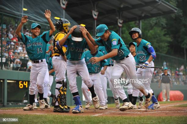 Right fielder Tang Fu Chen of Asia Pacific is mobbed by his teammates after coming home after a home run against the Caribbean in the international...