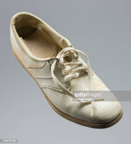 Right golf shoe worn by African-American golfer Ethel Funches. The shoe is off white and has some dirt stains on it. The quarter on either side of...