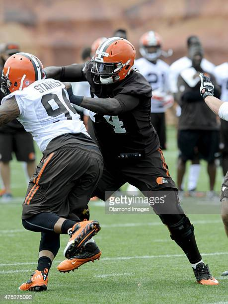 Right guard Cameron Erving of the Cleveland Browns engages defensive tackle Randy Starks during a mini camp practice on May 26 2015 at the Cleveland...