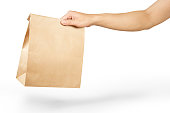 Right hand holding a brown paper bag isolated on white with clipping path.