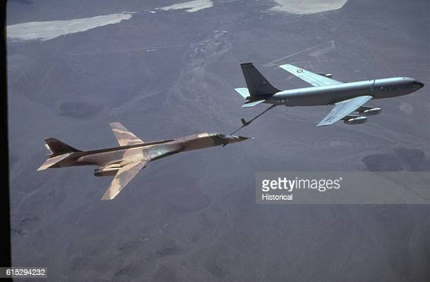 A right side view of a B bomber aircraft being refueled by a KC135 Stratotanker aircraft over the base range during testing and evaluation | Location...